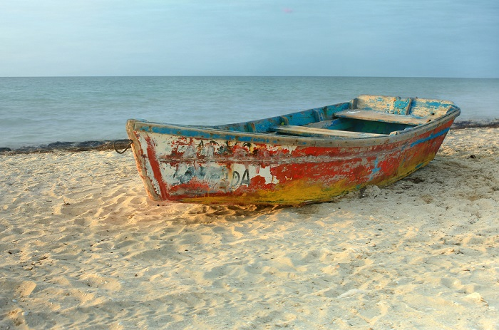 Solo rowboat with peeling paint resting on sandy beach