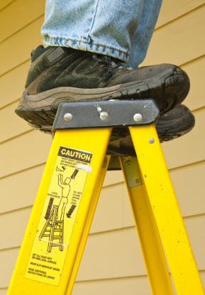 man standing on the top step of a ladder with caution sticker showing danger